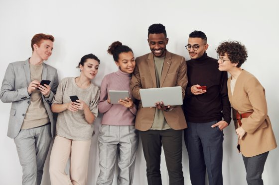 A group of young professionals looking at a computer.